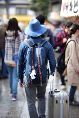 A man in a denim dress and a blue hat with a backpack and a suitcase road in the tourist center.
