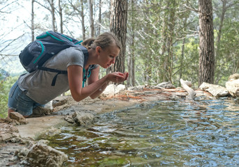 Woman with backpack drinking water from mountain spring.
