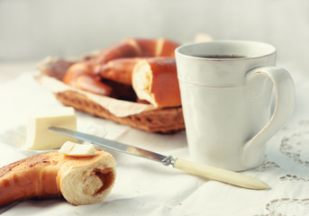 Fresh baked croissants, a saucer with butter and a cup of coffee on a white tablecloth background. toned picture. close up and selective focus