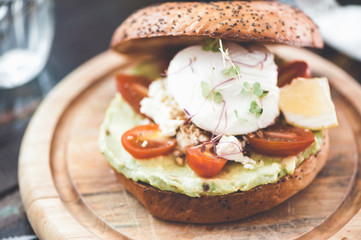bagel with avocado, tomatoes and poached egg close up