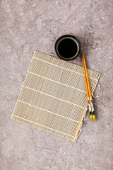 Bamboo mat for cooking sushi, soy sauce and chopsticks on a gray stone background