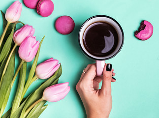 Woman's hand holding cup with coffee and pink tulips