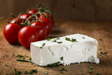 Feta cheese with bunch of cherry tomatoes in background on wood