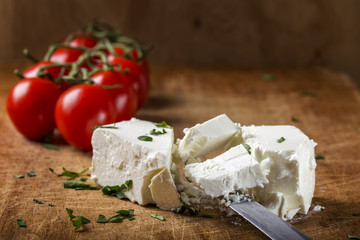 Feta cheese with knife and bunch of cherry tomatoes in background