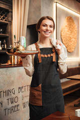 Amazing young woman waiter standing in cafe.