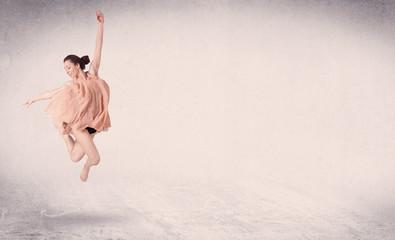 Modern ballet dancer performing art jump with empty background