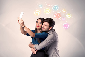 Happy couple taking selfie with smiley