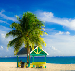 Man sitting in a colorful hut on West Bay Beach in the Caribbean looking at the sea, Grand Cayman, Cayman Islands