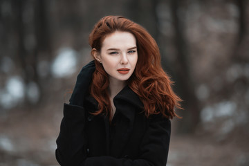Portrait of a glamorous girl with long red hair in black clothes. A woman in a black coat posing on a background of winter, autumn nature. Female street fashion style. Beautiful elegant model