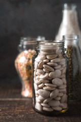 Bank with white beans, lentils on the table