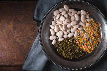Placer green and white beans, lentils in a wooden bowl and a napkin