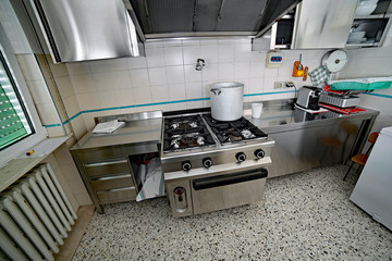 industrial kitchen with steel furniture and a aluminum pot on th