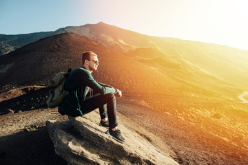 Man sitting on rock at sunrise on background of volcano Etna mountain in Sicily