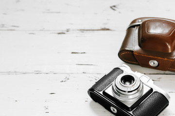 Old film camera in brown vintage case  on white wood background. top view