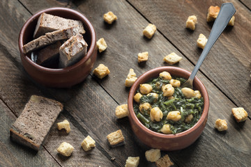 Chickpea stew with spinach on rustic wooden background. Traditional Spanish recipe.