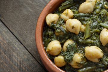Close up of Chickpea and spinach stew on rustic wooden background. Spanish tapas.