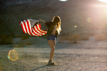 Woman in sunlight holding American flag