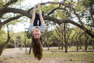 Woman hanging upside down from tree branch