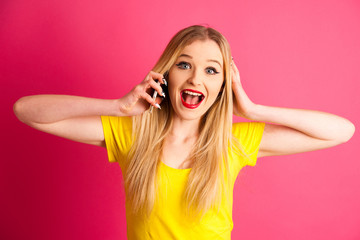 excited blonde teenage girl talking on smart phone over pink background