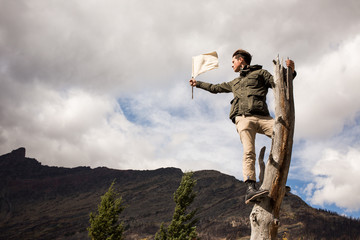 Man standing on tree trunk holding flag