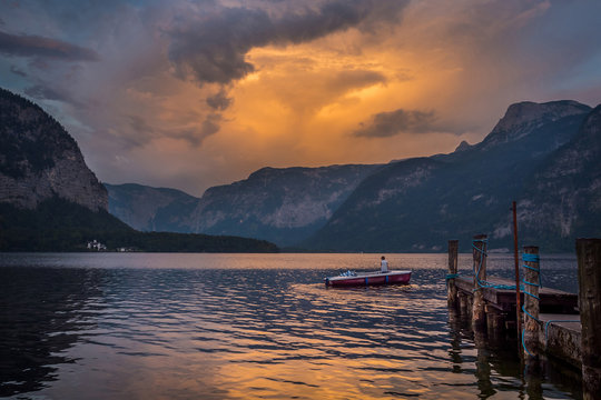 A man in a boat on the lake on sunset in Austria