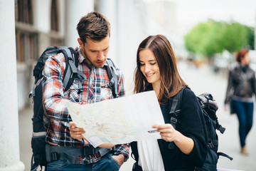 Backpacker couple traveling looking at map