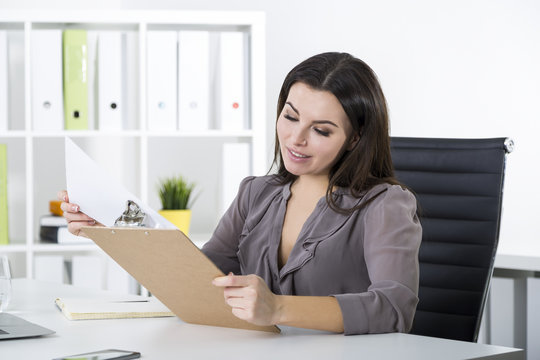 Side view of a woman in gray looking at clipboard