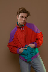 Cute guy in hipster clothes 90s posing in studio