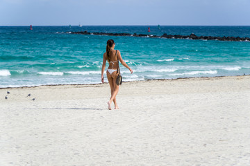 A young, athletic woman walks or strolls on the beach in a white bikini on a sunny summer day