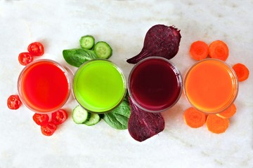 Four types of juice with scattered vegetables, above view over a white marble background