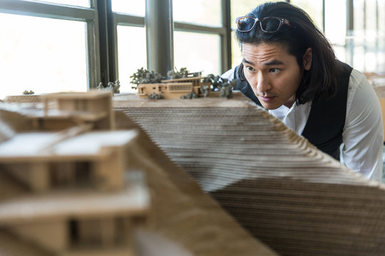Lead architect designer reviews physical model of structure built in 3d