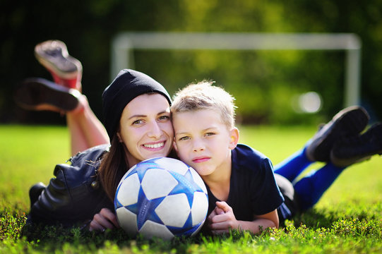 Young mother and her little boy playing a soccer game on sunny summer day