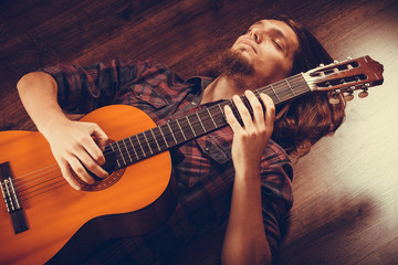 The man enjoys the moment with his guitar.
