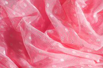 The texture of fabric lace with sequins on fabric background. Magenta, Hot pink, Cerise
