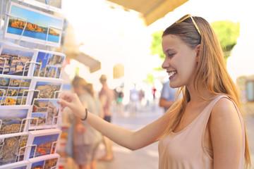 Blonde girl choosing postcards