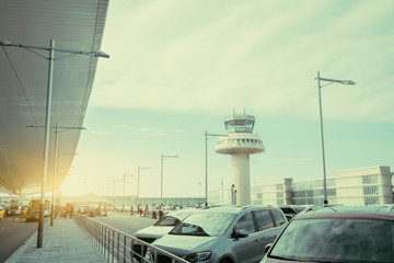 Parking lot and road near modern contemporary airport terminal in front of air traffic control tower, with many passengers and staff passing in distance, Barcelona, Spain