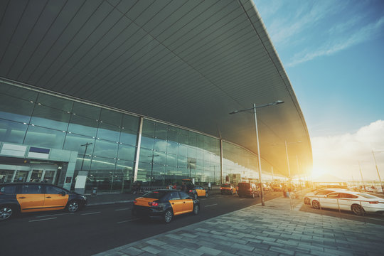 Cabstand in front of modern airport doors in Barcelona, cabrank with a lot of taxis near windowed facade of contemporary Airport terminal in Spain with road, long ceiling and parking lot