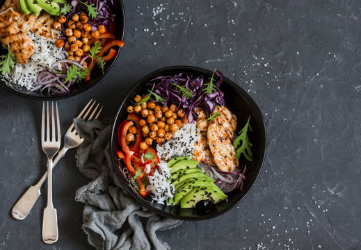 Grilled chicken, rice, spicy chickpeas, avocado, cabbage, pepper buddha bowl on dark background, top view. Delicious balanced food concept