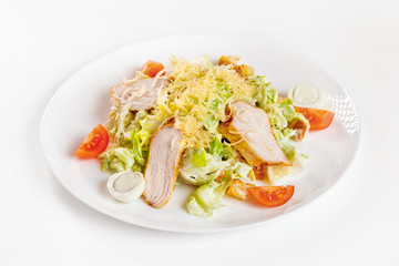 Closeup image of caesar salad with chicken on plate isolated at white background.