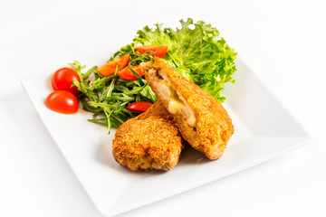 Fried golden chicken with cheese and vegetables on plate isolated at white background.