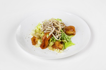 Plate of fresh calamari salad with vegetables isolated at white background.
