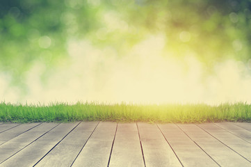 Wooden plank and bright spring green leave bokeh background ,adjust to vintage tone
