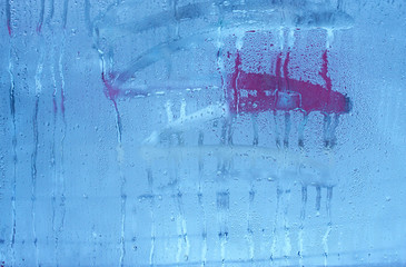 The condensate in the form of water droplets on the background window. Window glass with high humidity, condensation, large drops of water running down the window cold tone