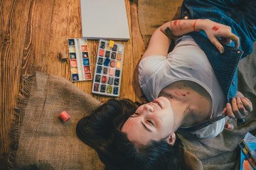 Woman lying on the floor paint all over her