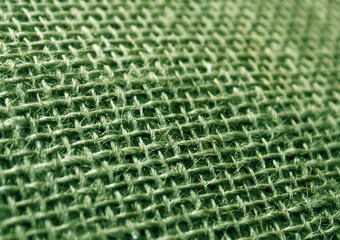 Green color hessian cloth sack texture with blur effect.