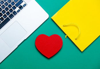 beautiful heart shaped toy, cool shopping bag and modern silver laptop on the wonderful blue background