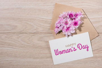Womans Day tag paper with color flowers on wooden background. Top view.