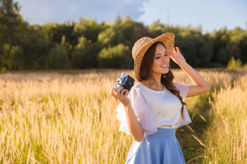 Girl in hat shooting photo walking in golden dried grass field with camera