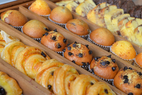 Assorted pastries in wooden box (chocolate chip muffin, butter cake, croissant)