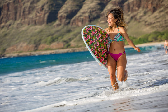 surfing girl with surboard running on a sandy beach